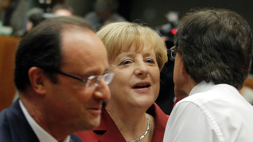German Chancellor Angela Merkel, center, is greeted by Belgian Prime Minister Elio Di Rupo, right, as French President Francois Hollande, left, walks by during a round table meeting at an EU summit in Brussels, Thursday, Oct. 24, 2013. A two-day summit meeting of EU leaders is likely to be diverted from its official agenda, economic recovery and migration, after German Chancellor Angela Merkel complained to U.S. President Barack Obama that U.S. intelligence may have monitored her mobile phone. (AP Photo/Yves Logghe)