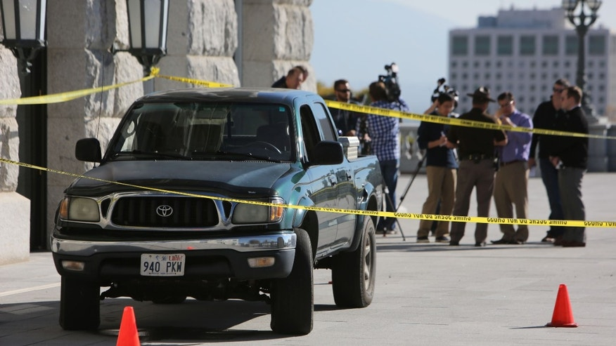 The pickup truck driven up several flights of steps to the west entrance of the Utah State Capitol in Salt Lake City Tuesday Oct. 22, 2013, sits behind crime scene tape.  Utah state troopers used a stun gun to arrest the man who drove the pickup truck.  (AP Photo/The Salt Lake Tribune, Francisco Kjolseth)  DESERET NEWS OUT; LOCAL TV OUT; MAGS OUT