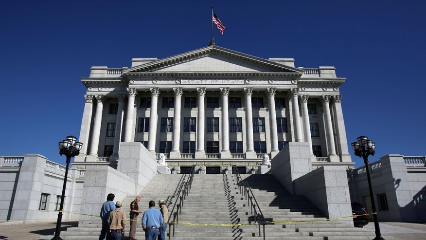 People gather at the base of the steps leading to the west entrance to the Utah State Capitol in Salt Lake City Tuesday Oct. 22, 2013, after a man drove a pickup truck up the steps to the entrance. Utah state troopers used a stun gun to arrest the man who drove the pickup truck.  (AP Photo/The Salt Lake Tribune, Francisco Kjolseth)  DESERET NEWS OUT; LOCAL TV OUT; MAGS OUT