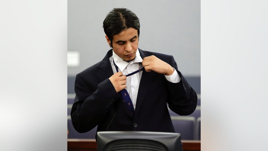 Mazen Alotaibi removes his tie before returning to the detention center after the reading of his verdict, Wednesday, Oct. 23, 2013, at Clark County District Court in Las Vegas. The jury found the Saudi Arabian air force sergeant guilty of sexually assaulting a 13-year-old boy at a Las Vegas Strip hotel last New Year's Eve. He could face a sentence of 35 years to life in prison. (AP Photo/Julie Jacobson)