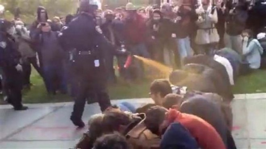 Friday, Nov. 18, 2011: A police officer uses pepper spray as he walks down a line of Occupy demonstrators sitting on the ground at the University of California, Davis. (AP)