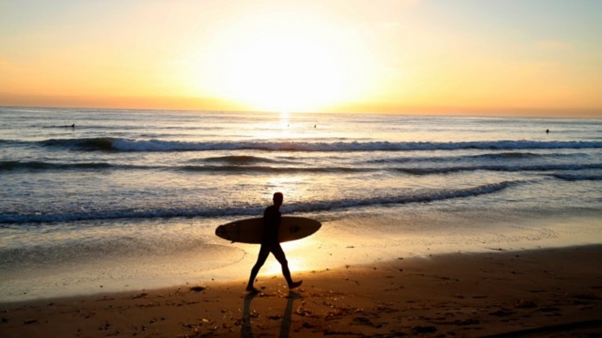 Sept. 18, 2013: A surfer walks with his surfboard as he heads home from the beach in Leucadia, Calif.