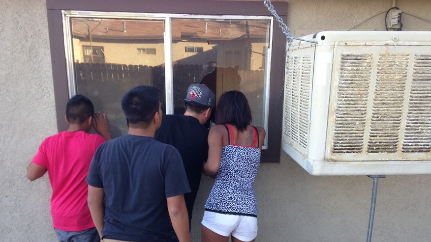 Passersby peer into a house Friday Oct. 25, 2013, where gunman Sergio Munoz shot two people, a man and a woman, killing the woman, before leading police on a chase through the Mojave Desert, before being shot and killed by police near Ridgecrest, Calif. (AP Photo/Justin Pritchard)