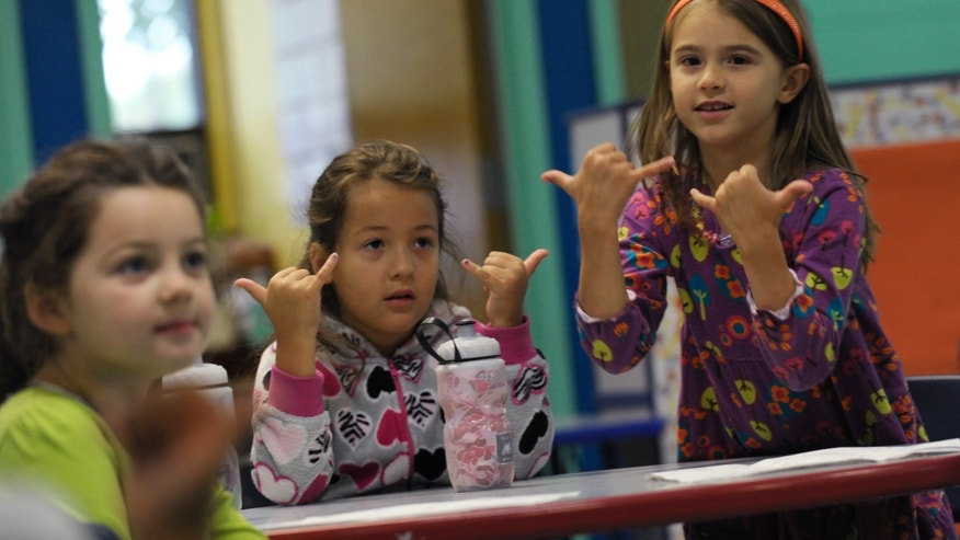 Oct. 9. 2013: In this photo from left, Brooklyn Olds, and Grace Whittaker learn sign language during a lesson at a home schooling co-operative at Andrews Air Force Base, Md.