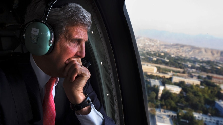 FILE - In this Oct. 11, 2013, file photo U.S. Secretary of State John Kerry looks out the window en route to the ISAF headquarters after an unannounced visit to Kabul, Afghanistan. President Barack Obama and Kerry are trying to quell international anger over the latest classified disclosures about NSA tactics by Edward Snowden, who is still in Russia. Those revelations, including the alleged tapping of up to 35 world leaders' cell phones, are threatening to undermine America's ability to put its imprint on world affairs. (AP Photo/Jacquelyn Martin, Pool)