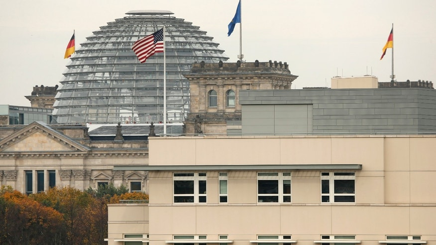 The American flag flies on top of the U.S. embassy in front of the  Reichstag building  that houses the German  Parliament, Bundestag, in Berlin, Friday, Oct. 25, 2013. European Union leaders on Friday vowed to maintain a strong trans-Atlantic partnership despite their anger over allegations of widespread U.S. spying on its allies. France and Germany insist new surveillance rules should be agreed with the United States by the end of the year.. On Thursday's opening day of the summit, the spying issue united the 28 EU leaders in criticizing the snooping  after allegations surfaced that German Chancellor Angela Merkel had one of her mobile phones tapped by U.S. services. (AP Photo/Michael Sohn)