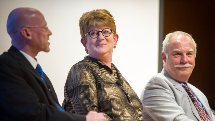 "Kathleen Carroll, executive editor and senior vice president of The Associated Press, center, listens to the commentary of fellow panelist Gary Ross, left, during a panel discussion titled ""Is Journalism a Crime?"" at the 80th Annual Associated Press Media Editors' conference at the Indiana State Museum in Indianapolis Monday, Oct. 28, 2013. (AP Photo/Doug McSchooler)"