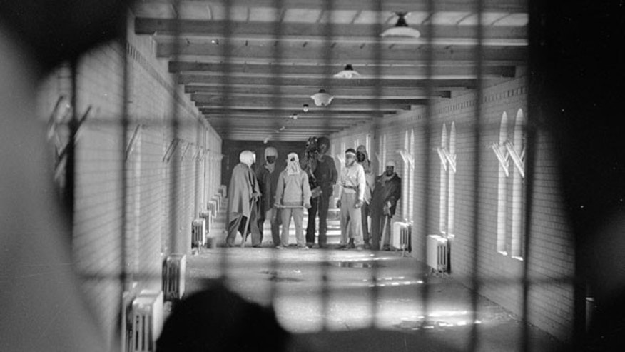 FILE - In this Sept. 10, 1971 file photo, inmates wearing cloaks and football helmets stand behind bars in a corridor leading to D block as they begin negotiations with New York State officials after a prison uprising at Attica State Prison, in Attica, N.Y. (AP Photo/Bob Schutz, File)