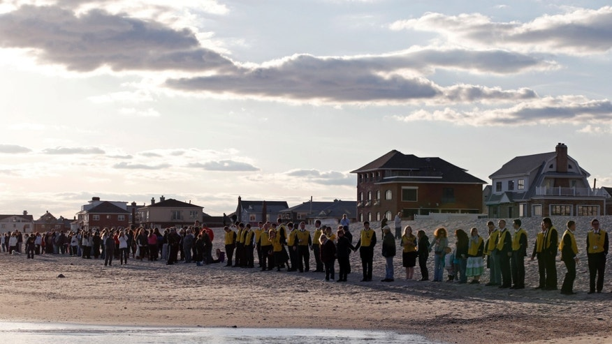 "Oct. 27, 2013: People line up along the beach in the Belle Harbor section of the Rockways during the ""Rockaway Rising:  Hands Across the Sand,"" beachside ceremony commemorating the one year anniversary of Superstorm Sandy, in New York. The actual one year anniversary of Superstorm Sandy is Tuesday, Oct. 29."