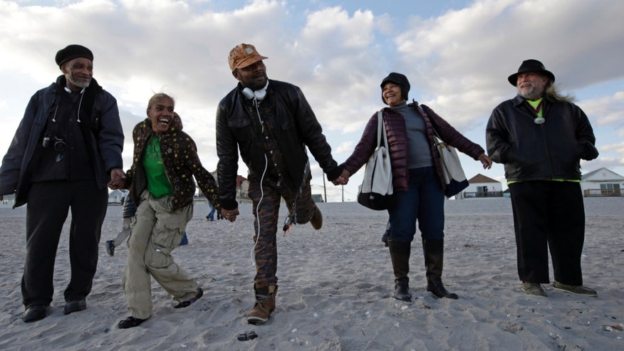 "Oct. 27, 2013: From left, Thomas Robinson, Debiorah Roman, Carl Myrie and his mother Maureen, join other residents of Arverne on the Sea at they participate in a beachside ceremony ""Rockaways Rising: Hands Across the Sand,"" beach side ceremony commemorating the one year anniversary of Superstorm Sandy in New York. The actual one year anniversary of Superstorm Sandy is Tuesday, Oct. 29."