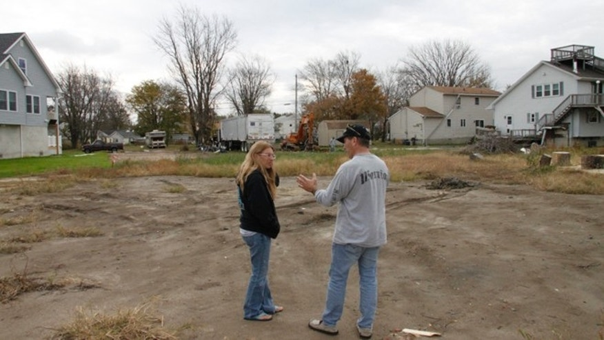 Bob and Pam Vasquez survey the empty lot in Union Beach, NJ where their house once stood.