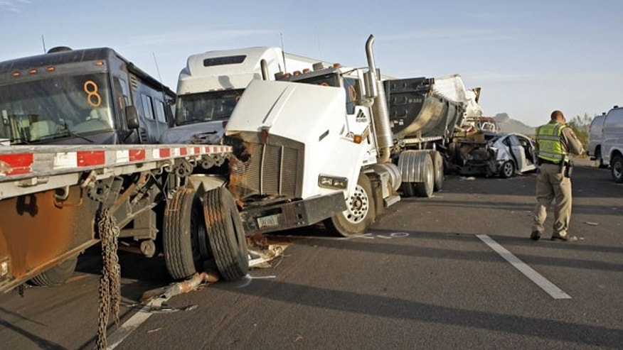 October 29, 2013: Arizona Department of Public Safety officers investigate a multiple fatality accident involving six semi tractor-trailers and 19 other vehicles in the eastbound lanes of Interstate 10 south of Casa Grande, Ariz. Authorities say three people are dead and at least 12 others injured after a dust storm led to chain-reaction collisions. (AP Photo/Arizona Daily Star, Ron Medvescek)
