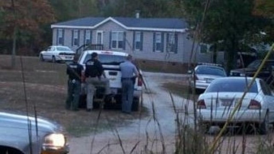 October 29, 2013: Sheriff's deputies gather outside a house where six people, including two children, died in a shooting in Greenwood, S.C. (FoxCarolina.com)