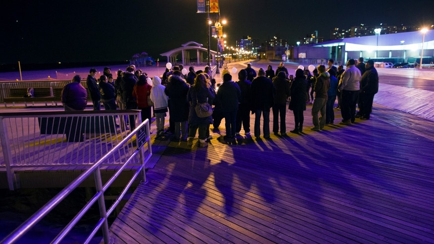 People gather on the boardwalk near the Coney Island Pier Tuesday, Oct. 29, 2013, to mark the anniversary of Superstorm Sandy and its landfall in New York at approximately this same time of day one year ago. (AP Photo/Craig Ruttle)