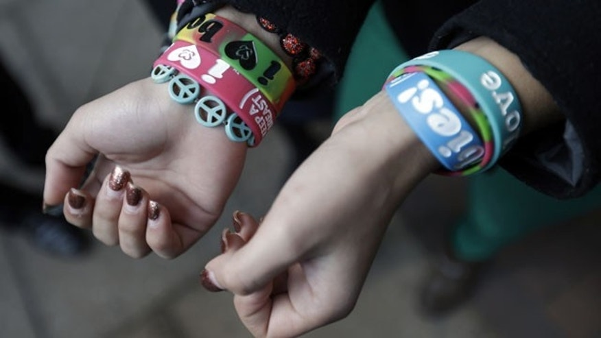 "FILE - In this Feb. 20, 2013 file photo, Easton Area School District students Brianna Hawk, 15, left, and Kayla Martinez, 14, display their ""I (heart) Boobies!"" bracelets for photographers outside the U.S. Courthouse in Philadelphia. (AP Photo)"