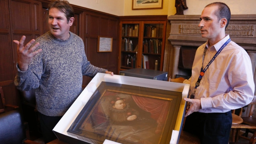 "Oct. 29, 2013: Scott Krafft, left, curator of the Charles Deering McCormick Library of Special Collections in Evanston, Ill., and manuscript librarian Benn Joseph, display a painting of a dead Spanish boy from the 1,600s. The portrait is one of the artifacts from the ""Death Collection"" --  an archive of death-related oddities once owned by horror novelist and screenwriter Michael McEachern McDowell that have been purchased by Northwestern University."