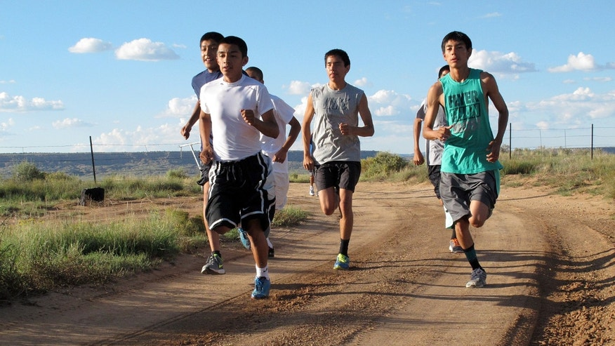 In this Friday, Oct. 13, 2013 photo, members of the Hopi High School boys cross-country team head down a trail near Polacca, Ariz. Hopi High School has earned 23 state cross-country titles in a row. But this is not only about sports. This is about the enduring spirit of a culture, where running is rooted in this tribe's tradition.  (AP Photo/Felicia Fonseca)
