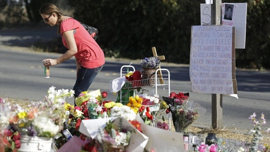 October 30, 2013: Robin Betts stops to place a candle at a memorial Wednesday in Santa Rosa, Calif., where Andy Lopez was killed last week by a sheriff's deputy. The 13-year-old boy was carrying a pellet gun that resembled an assault rifle (AP Photo)
