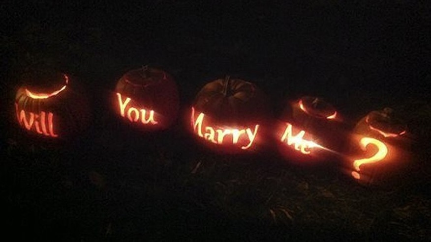 "This Oct. 30, 2013, photo shows five carved pumpkins strategically placed on the side of a hill by Zach Stoddard in Dayton, Ohio. Stoddard asked his girlfriend of three years, Lauren Brenneman to marry him. Brenneman said ""yes,"" much to the delight of the hundreds of people gathered Wednesday night for a popular neighborhood event called the Stoddard Avenue Pumpkin Glow. (AP/The Dayton Daily News, Amelia Robinson)"