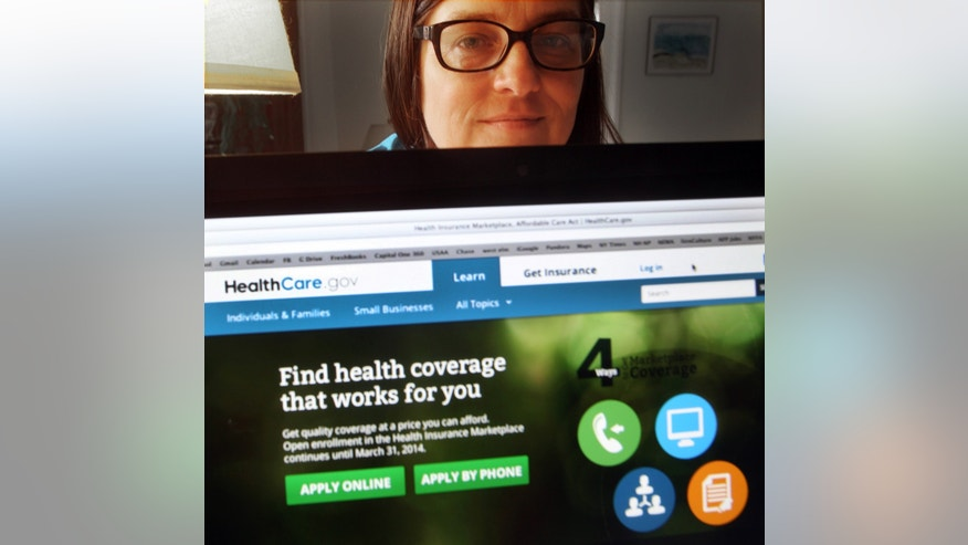 In a photo taken Monday Oct. 28, 2013, in Portsmouth, N.H., Deborah Lielasus poses behind her computer with the national health insurance enrollment website. Not long after she enrolled, the Department of Health and Human Services asked her to appear both in a video describing her experience and in photographs that could replace the stock photo on the insurance enrollment site. (AP Photo/Jim Cole)