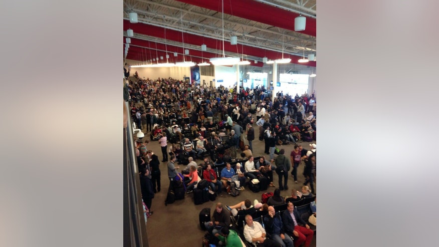 In this photo provided by Tory Belleci which has been authenticated based on its contents and other AP reporting, people wait in Los Angeles International Airport, Friday, Nov. 1, 2013.  Shots were fired Friday at Los Angeles International Airport, prompting authorities to evacuate a terminal and stop flights headed for the city from taking off from other airports. (AP Photo/Tory Belleci)