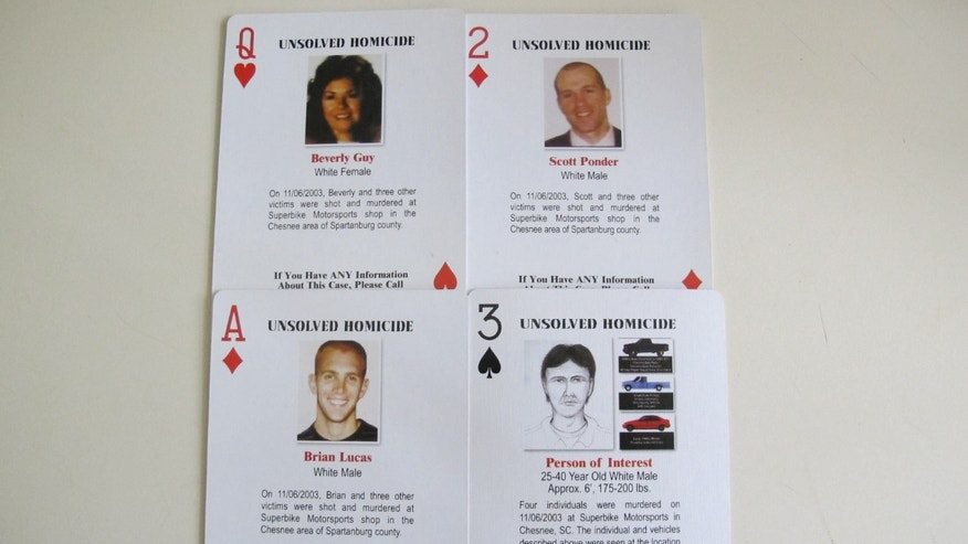 Details of a quadruple homicide are included on these playing cards passed out to inmates in South Carolina prisons in this Wednesday, Oct. 24, 2013, photo in Spartanburg, S.C. The cards were created by Tom Lucas, whose son, Brian, was killed in the unsolved shootings. Four people were killed inside a motorcycle shop in Spartanburg County on Nov. 6, 2003. Investigators have followed more than 750 leads but haven't made any arrests, leaving four victims' families searching for answers.  (AP Photo/Jeffrey Collins)