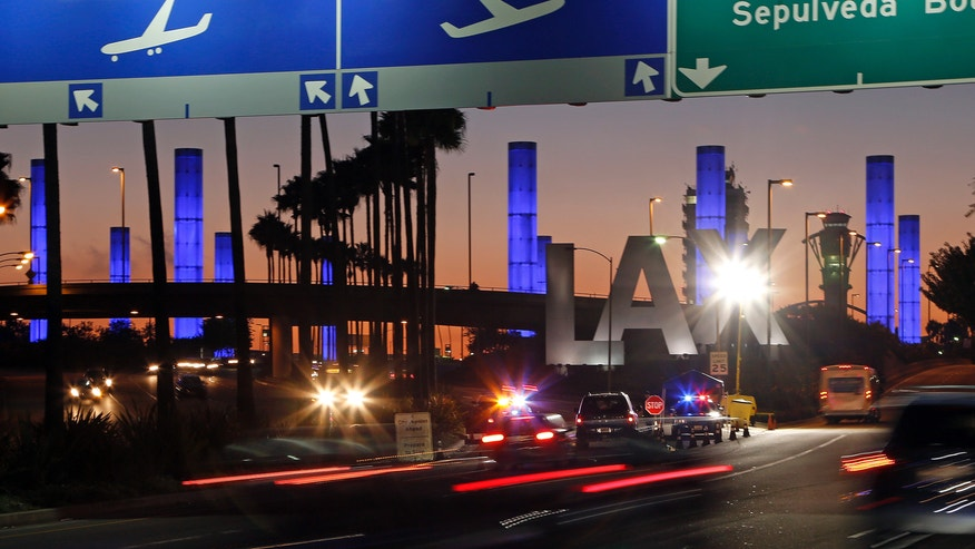 Lighted pylons at the Century Boulevard entrance to Los Angeles International Airport, which normally flash in a multicolored sequence, shine a steady blue Saturday evening, Nov. 2, 2013, in honor of Gerardo Hernandez, the Transportation Security Administration officer slain at an LAX terminal Friday. He is the first TSA officer to die in the line of duty in the history of the 12-year-old agency, created in the aftermath of the Sept. 11, 2001 terrorist attacks. A police entry checkpoint, part of an increased visible police presence, is seen in the foreground. (AP Photo/Reed Saxon)