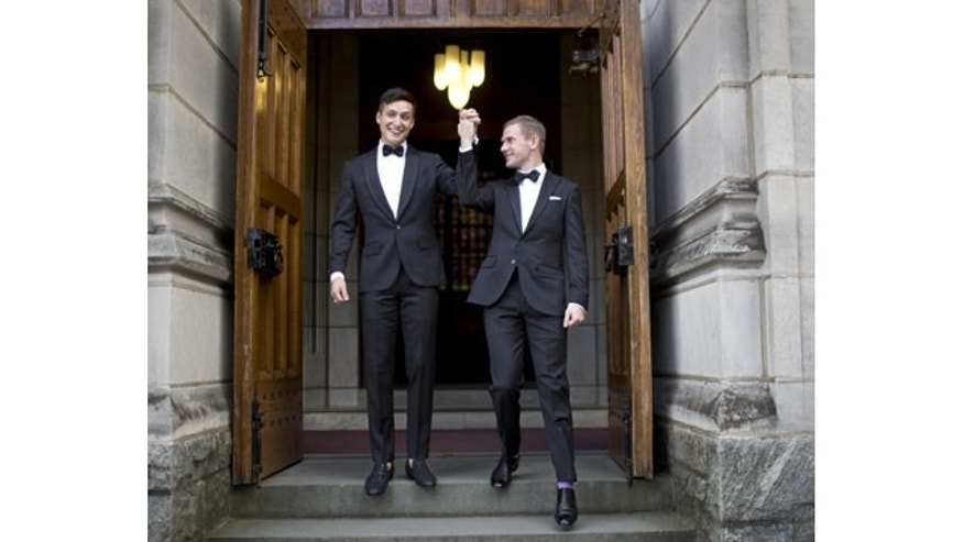November 2, 2013: West Point graduate Larry Lennox-Choate, left, and Daniel Lennox-Choate, leave church following their wedding ceremony on Saturday, Nov. 2, 2013, at the U.S. Military Academy's Cadet Chapel in West Point, N.Y. Choate and Lennox are the first men to wed at the chapel since New York legalized gay marriage in 2012. The chapel has already hosted two same-sex weddings of women in late 2012. (AP Photo/Jill Knight)
