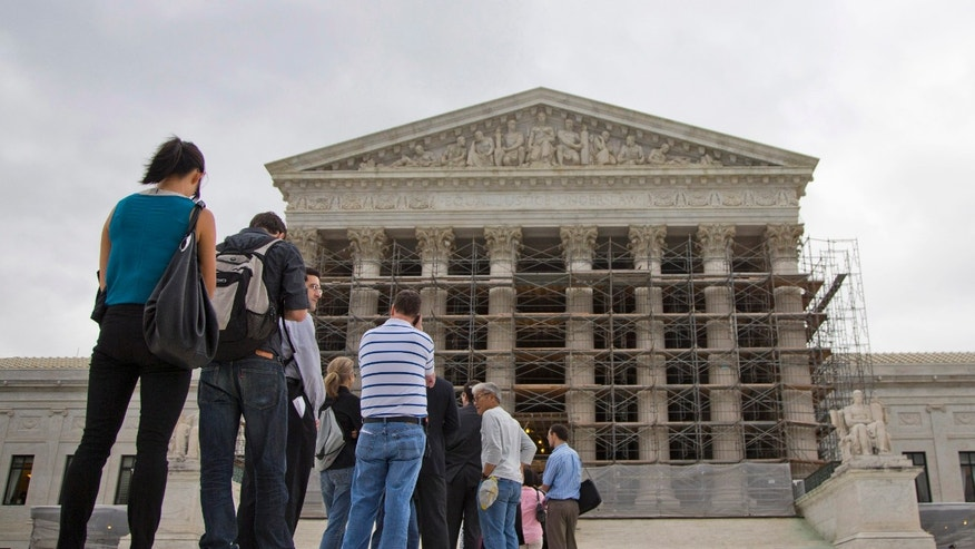 FILE - This Oct. 7, 2013 file photo shows people wait in line to enter the Supreme Court in Washington. The Supreme Court asks God for help before every public session. Now the justices will settle a dispute over prayers in the halls of government. The case before the court involves prayers said at the start of town council meetings in Greece, N.Y., outside of Rochester. It is the court's first legislative prayer case since 1983, when the justices said that an opening prayer is part of the nation's fabric and not a violation of the First Amendment. The federal appeals court in New York held that the town violated the Constitution by opening nearly every meeting over an 11-year span with prayers that stressed Christianity. (AP Photo/ Evan Vucci, File)