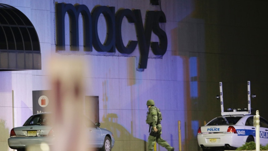 An official wearing tactical gear walks outside of Garden State Plaza Mall following reports of a shooter, Monday, Nov. 4, 2013, in Paramus, N.J. Hundreds of law enforcement officers converged on the mall Monday night after witnesses said multiple shots were fired there. (AP Photo/Julio Cortez)