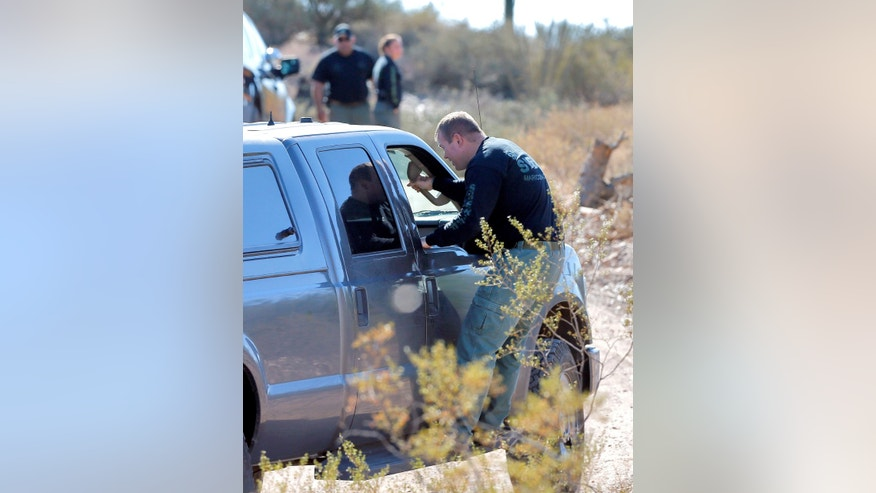 A Maricopa County Sheriff's deputy catches a ride along 27th Ave, Tuesday, Nov. 5, 2013, in New River, Ariz., just north of a property where authorities say a man lost most of his leg after an explosive detonated. Maricopa County Sheriff Joe Arpaio says the blast occurred late Monday at a residential property formerly owned by a man who had a munitions operation in the area several decades ago. (AP Photo/Matt York)