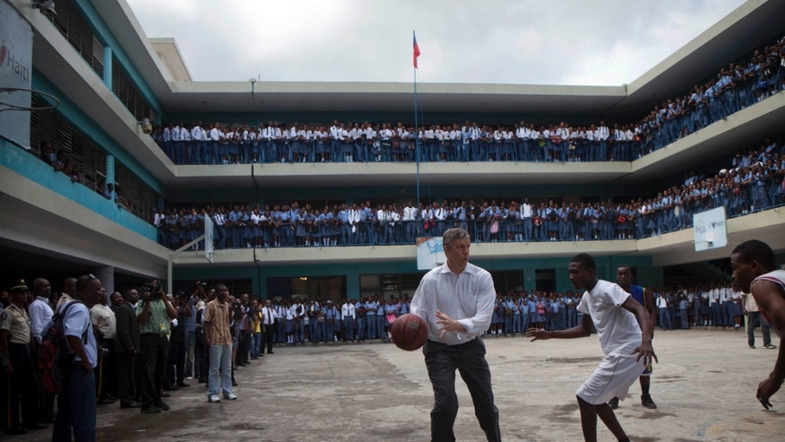 U.S. Secretary of Education Arne Duncan plays basketball with high school students during his visit to the Lycee de Petion-Ville school in Petion-Ville, Haiti, Tuesday, Nov. 5, 2013. Duncan was expected to announce a U.S. education aid package for Haiti during his two-day visit. (AP Photo/Dieu Nalio Chery)