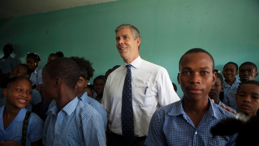 U.S. Secretary of Education Arne Duncan stands with students during his visit to Lycee de Petion-Ville high school in Petion-Ville, Haiti, Tuesday, Nov. 5, 2013. Duncan was expected to announce a U.S. education aid package for Haiti during his two-day visit. (AP Photo/Dieu Nalio Chery)