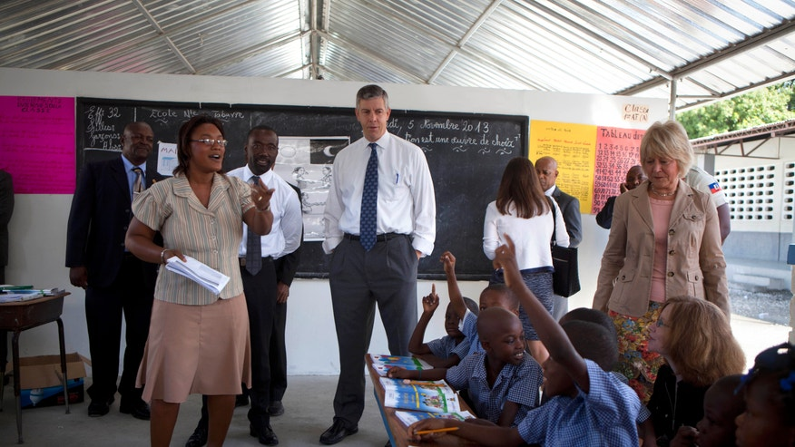 U.S. Secretary of Education Arne Duncan, center, stands in a classroom during his visit to the National School in Tabarre, Haiti, Tuesday, Nov. 5, 2013. Duncan was expected to announce a U.S. education aid package for Haiti during his two-day visit. (AP Photo/Dieu Nalio Chery)