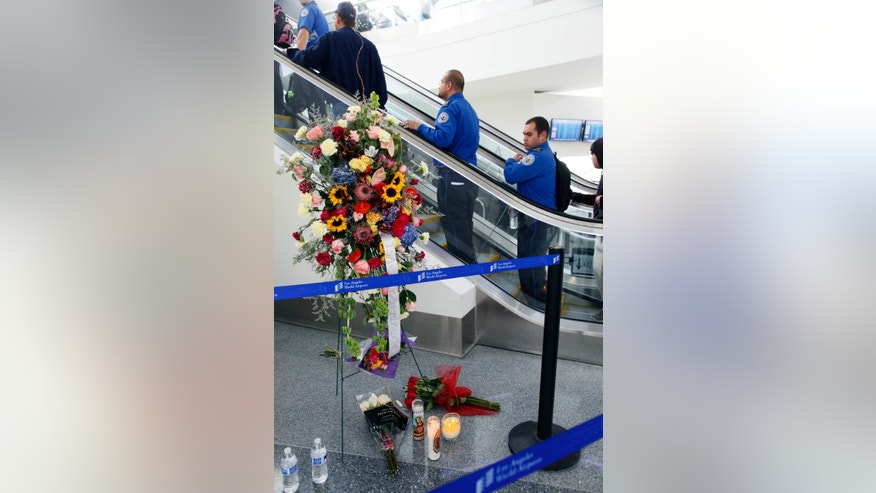 Transportation Security Administration officers ride an escalator past a memorial at Terminal 3 at Los Angeles International Airport Monday, Nov 4,  2013. TSA Officer Gerardo I. Hernandez was killed and two officers and one civilian wounded in the shooting at Terminal 3 Friday, Nov. 1. Operations at the airport were back to normal Monday, the first business day since the attack. (AP Photo/Nick Ut)