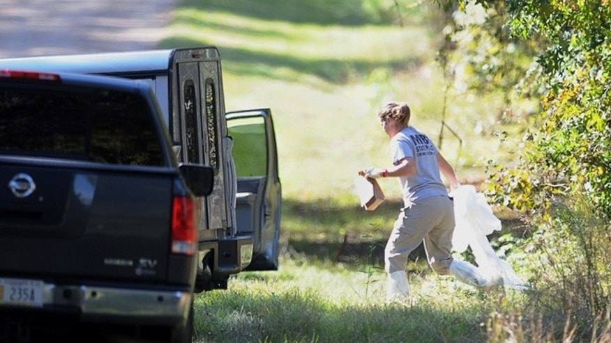 Nov.  5, 2013: An investigator carries items from the wooded area along Shelby Road in rural Copiah County, Miss., where the bodies believed to be of a missing Jackson-area family where discovered in an abandoned house. Copiah County Sheriff Harold Jones says the bodies were found in an abandoned house about a mile from where the family's vehicle was located Saturday.