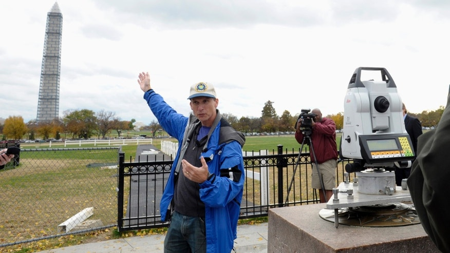 Dru Smith, Chief Geodesist of the National Geodetic Survey stands near a measurement device used to survey the height of the Washington Monument, Thursday, Nov. 7, 2013, in Washington. Surveyors are checking to make sure that the Washington Monument is still 555 feet, 5 1/8 inches tall. The survey is being conducted by the National Geodetic Survey and is the first of its kind since 1999. Surveyors can only access the peak of the monument to check the height when it's covered in scaffolding. The monument is undergoing repairs after it was damaged during a 5.8-magnitude earthquake in August 2011. (AP Photo/Susan Walsh)