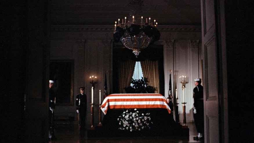 FILE - In this Nov. 23, 1963 file photo, the flag-draped casket of President John F. Kennedy lies in state in the East Room of the White House in Washington. The flag that draped the president's coffin and the saddle, sword and boots from the riderless horse in his funeral procession go on display Nov. 22 at the Kennedy Library on the 50th anniversary of Kennedy's assassination. (AP Photo, File)