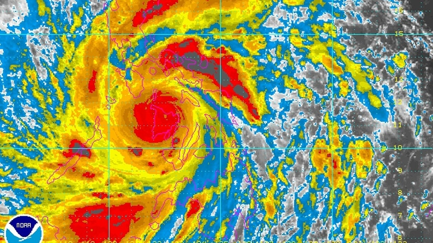 In this image provided by NOAA Friday Nov. 8, 2013 which was taken at 12:30 a.m. EST shows Typhoon Haiyan as it crosses the Philippines. One of the most powerful typhoons ever recorded slammed into the Philippines on Friday, setting off landslides, knocking out power in one entire province and cutting communications in the country's central region of island provinces. Weather officials say that Haiyan had sustained winds at 235 kilometers (147 miles) per hour, with gusts of 275 kph (170 mph) when it made landfall. (AP Photo/NOAA)