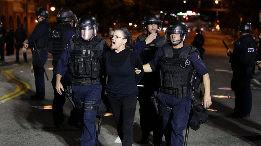 A protester chants her slogans as she is taken into custody after participating in a protest outside the new Chinatown Walmart store on Thursday, Nov. 7, 2013, in Los Angeles. Los Angeles police have arrested more than 50 people in the protest of more than 200 people. (AP Photo/Jae C. Hong)