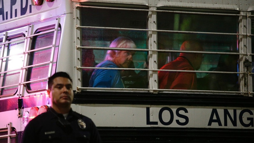 Demonstrators sit in a police bus as they are taken into custody after participating in a protest outside the new Chinatown Walmart store on Thursday, Nov. 7, 2013, in Los Angeles. Los Angeles police have arrested more than 50 people in the protest of more than 200 people. (AP Photo/Jae C. Hong)