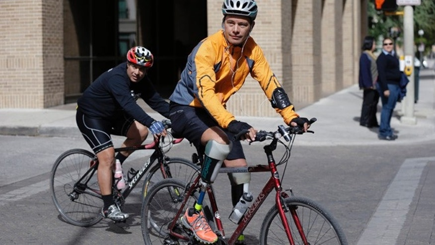 Nov. 7, 2013: Cyclist Carlos Gutierrez, right, a double amputee, rides his bike in San Antonio. Gutierrez, a Mexican asylum seeker who fled to the U.S. after extortionists cut his legs off for not paying the extortion fees, has ridden his bike from El Paso, Texas to Austin, Texas, to raise awareness on the situation of political asylum seekers.