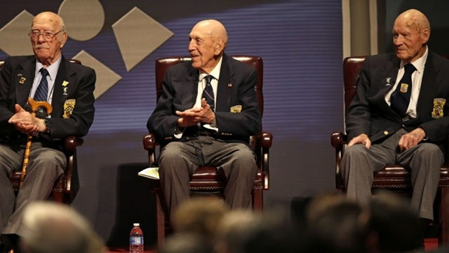 November 9, 2013: Three of the four surviving members of the 1942 Tokyo raid led by Lt. Col. Jimmy Doolittle, left to right, Edward Saylor, Richard Cole, and David Thatcher, applaud a speaker during their final toast celebration at the National Museum of the US Air Force in Dayton, Ohio. The fourth surviving member, Robert Hite, was unable to travel to the ceremonies. (AP Photo/Al Behrman)