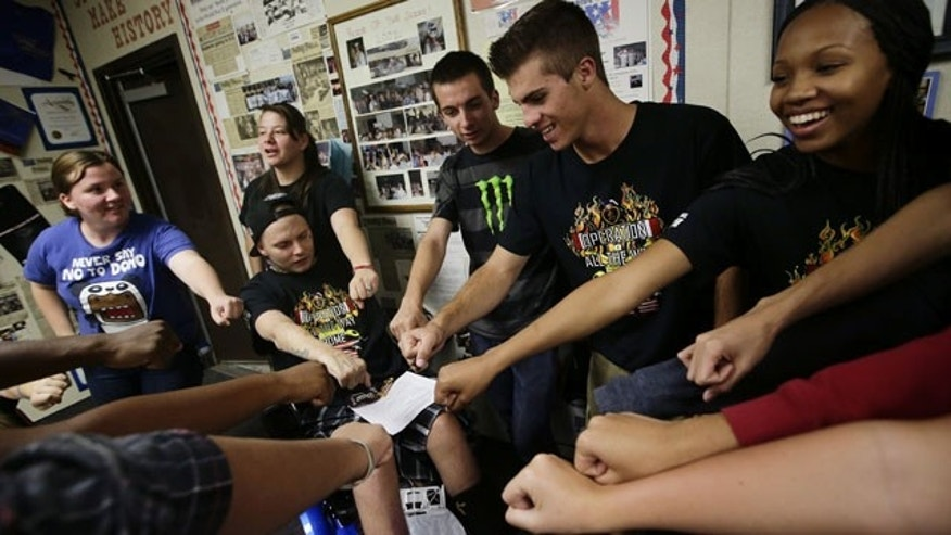 October 21, 2013: 27-year-old Iraq war veteran Jerral Hancock, sitting on an electric wheelchair, and members of Operation All The Way Home(OATH) chant their slogans after a meeting at Lancaster High School in Lancaster, Calif. The seniors in Jamie Goodreau's high school history class learned Hancock was stuck in a modest mobile home for months, unable to travel the 70 miles to the nearest VA hospital in Los Angeles to have his bedsores treated or his rotting teeth fixed. Goodreau's students, who each year raise a few thousand dollars for veterans, decided to make Hancock their cause. (AP Photo)