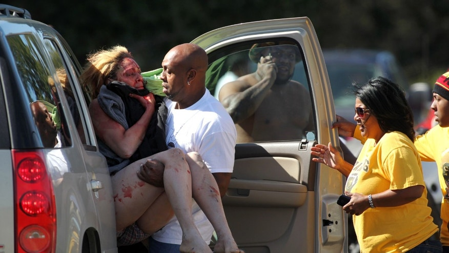 Marcus Arceneaux carries his wounded niece, Bethany Arceneaux, left, to a vehicle after she was rescued from a vacant house on Anderson Road on Friday, Nov. 8, 2013, in Duson, La. Bethany was allegedly kidnapped by Scott Thomas Wednesday evening in Lafayette, La. (AP Photo/The Lafayette Daily Advertiser, Leslie Westbrook) NO SALES