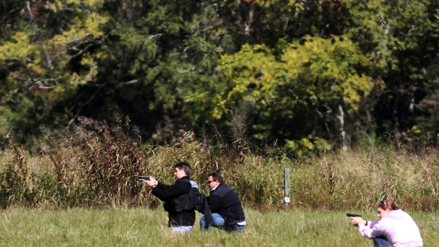 Police surround a vacant house off Anderson Road after search volunteers discovered a suspected kidnapper and his alleged victim on Friday, Nov. 8, 2013, in Duson, La. (AP Photo/The Lafayette Daily Advertiser, Leslie Westbrook) NO SALES