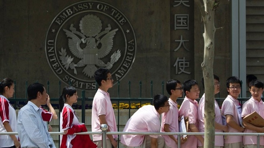 In this May 2012 file photo, Chinese students wait outside the U.S. Embassy for their visa application interviews in Beijing, China, Wednesday, May 2, 2012.  Hundreds of thousands of Chinese students are flocking to U.S. colleges and universities, helping to drive the number of international students studying in America to record levels, according to a report to be released Monday.