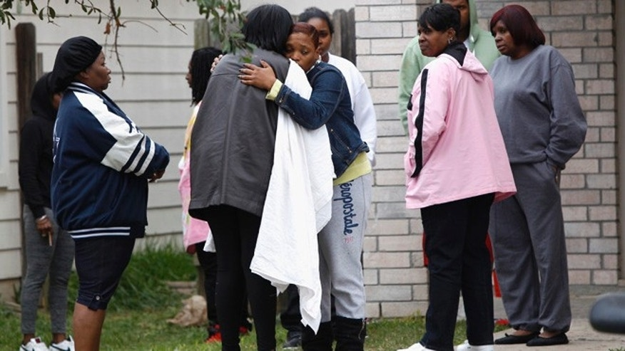 Nov. 10, 2013: Family and friends console each other outside 7318 Enchanted Creek in Cypress, Texas, after two people were killed when gunfire rang out at a large house party in a Houston suburb, sending partygoers fleeing in panic, authorities said.
