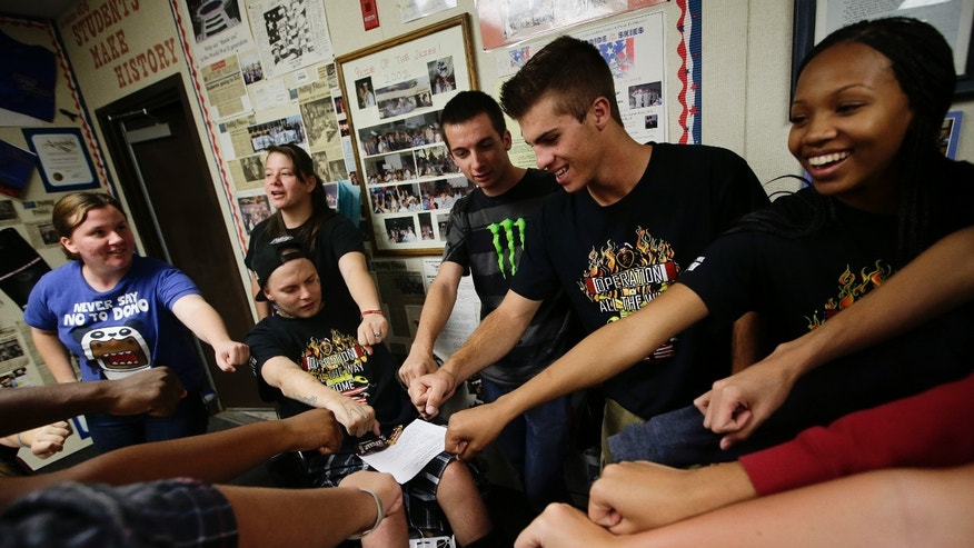 27-year-old Iraq war veteran Jerral Hancock, sitting on an electric wheelchair, and members of Operation All The Way Home(OATH) chant their slogans after a meeting at Lancaster High School on Monday, Oct. 21, 2013, in Lancaster, Calif. The seniors in Jamie Goodreau's high school history class learned Hancock was stuck in a modest mobile home for months, unable to travel the 70 miles to the nearest VA hospital in Los Angeles to have his bedsores treated or his rotting teeth fixed. Goodreau's students, who each year raise a few thousand dollars for veterans, decided to make Hancock their cause. (AP Photo/Jae C. Hong)
