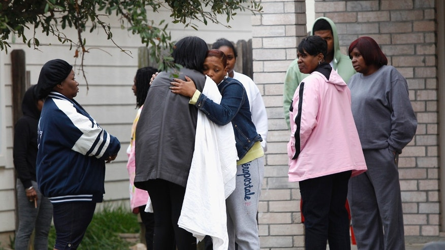 FILE - In this Nov. 10, 2013 file photo, family and friends console each other outside a home in Cypress, Texas, the morning after two people were killed and 19 were injured when gunfire rang out at a house party. Willie Young, 21, and Randy Stewart, 18, were arrested in connection with the shooting Monday, Nov. 1, 2013 according to the Harris County Sheriff's Office. Young is charged with deadly conduct while Stewart is charged with aggravated assault. (AP Photo/Bob Levey, File)